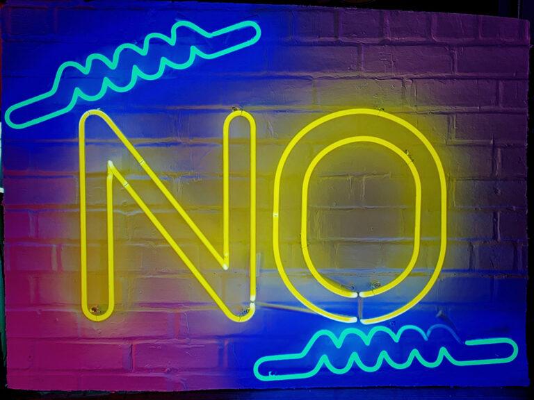 """Grote gele neon letters """"no"""" tegen een muur. Ik verslaafd? neen hoor. Verslaving wordt daarom ook ziekte van ontkenning genoemd."""