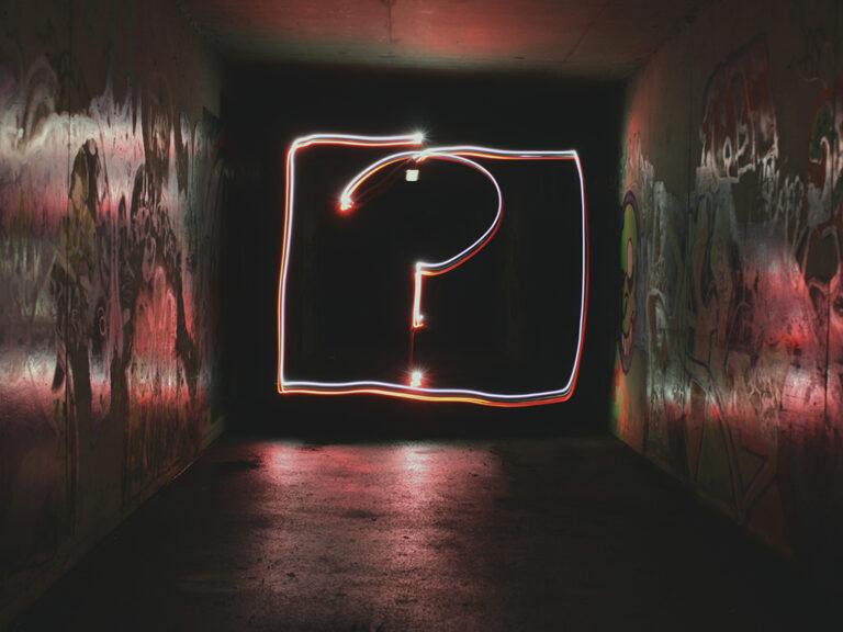 """Groot neon vraagteken geprojecteerd in een donkere steeg met street art. Het reflecteert het zoeken van de verslaafde naar het """"waarom""""."""
