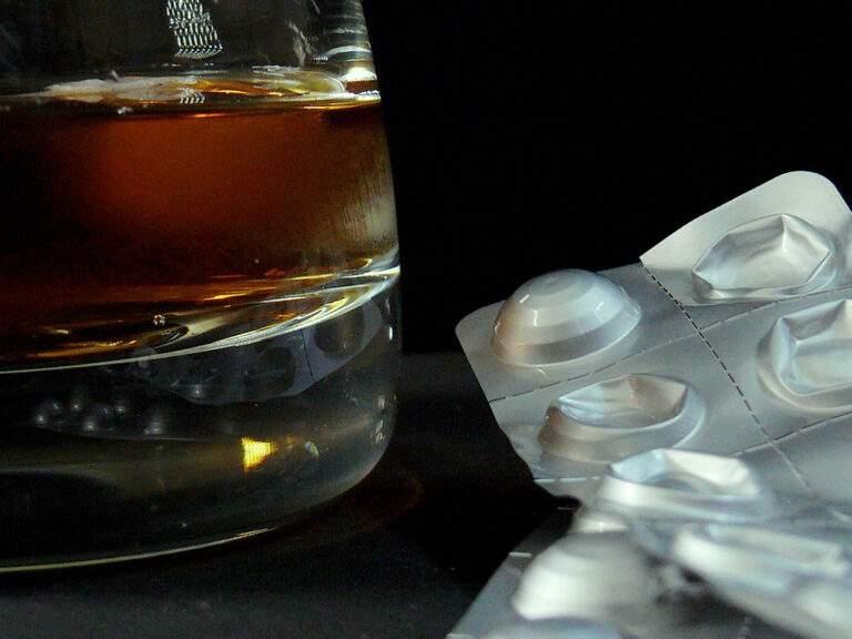 Op tafel staat een glas alcohol en strips medicatie. Een alcoholverslaving inruilen voor een medicatieverslaving is een voorbeeld van cross addiction.
