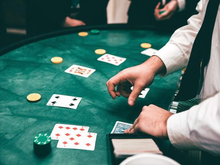 Handen van croupier in casino aan speeltafel, met spelers. Werd hoger ingezet om schulden terug te verdienen? Dan kan het gokgedrag problematisch zijn.