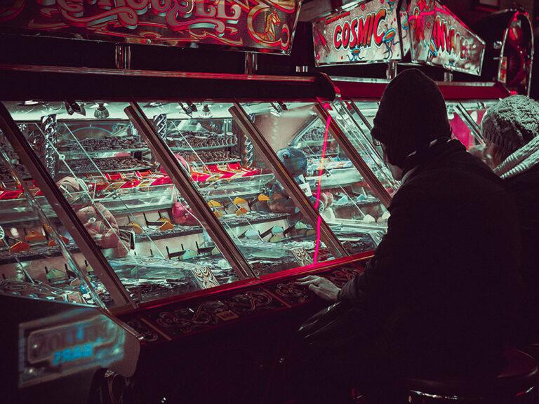 Man speelt een gokspel in een lunapark. Hij heeft alleen nog oog voor het spel. Bij een onweerstaanbare drang om te gokken is er gokverslaving.