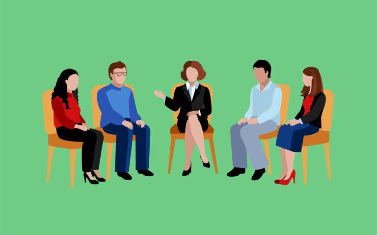 Rond de verslavingstherapeut zitten 4 mensen die deelnemen aan de groepssessie. Hierdoor vergroot hun kans op herstel.