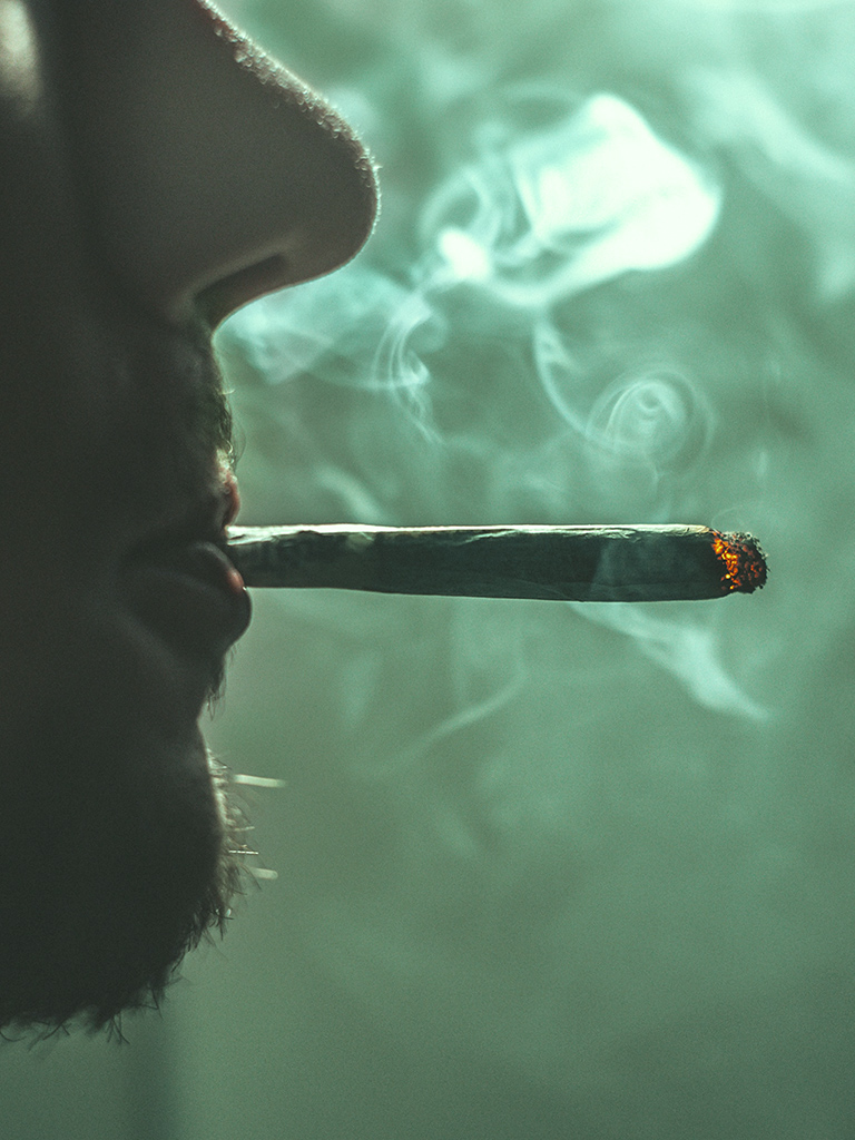 Deel van gezicht van man met dampende joint in mond. Ook recreatief gebruik van drugs kan voor problemen zorgen in je leven.