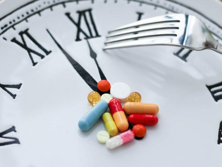 Hoop medicijnen op klok met wijzerstand 5 voor 12; een vork om medicatie op te eten. Hoog tijd om je medicijngebruik in vraag te stellen.