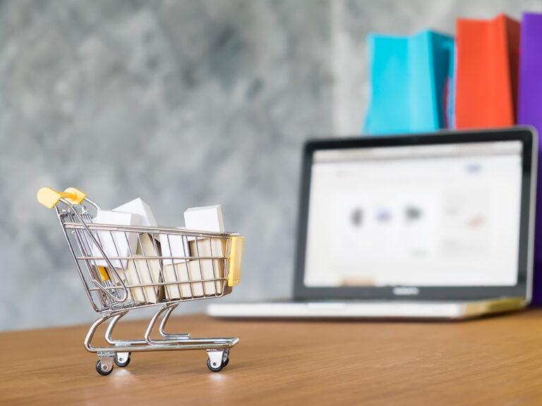 Winkelkar in miniatuur is volgeladen met pakjes, en staat naast laptop op bureau. Online kopen is mogelijk 24/7 en is daarom heel verleidelijk.
