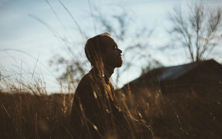 Jonge man in kleermakerszit in veld mediteert. Mediteren en mindfulness is zinvol bij herstel van verslaving om dwanggedachten te stoppen.