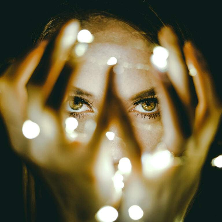 Ogen van vrouw die vingers voor haar gezicht spreidt. Brainspotting is therapie die werkt met de ogen waarbij beoogd wordt dat hersenen zichzelf herstellen.