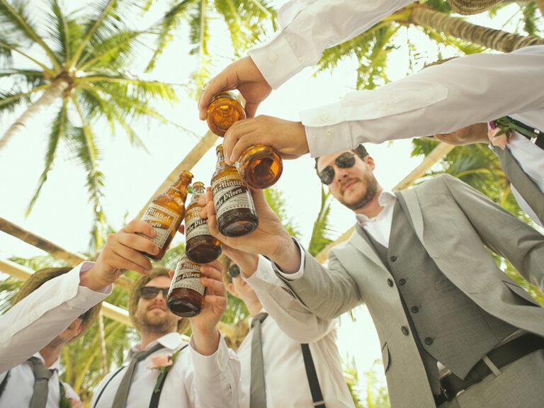 Een aantal mannen in feestpak toosten samen met een flesje bier in de hand. Sociaal geaccepteerd? Ja. Let op voor overmatig gebruik.