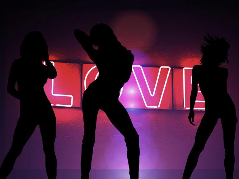 """Zwarte profielen van stripsters op podium voor rood neon licht met letters """"love"""". Waar seks een obsessie wordt, loert een sexverslaving?"""