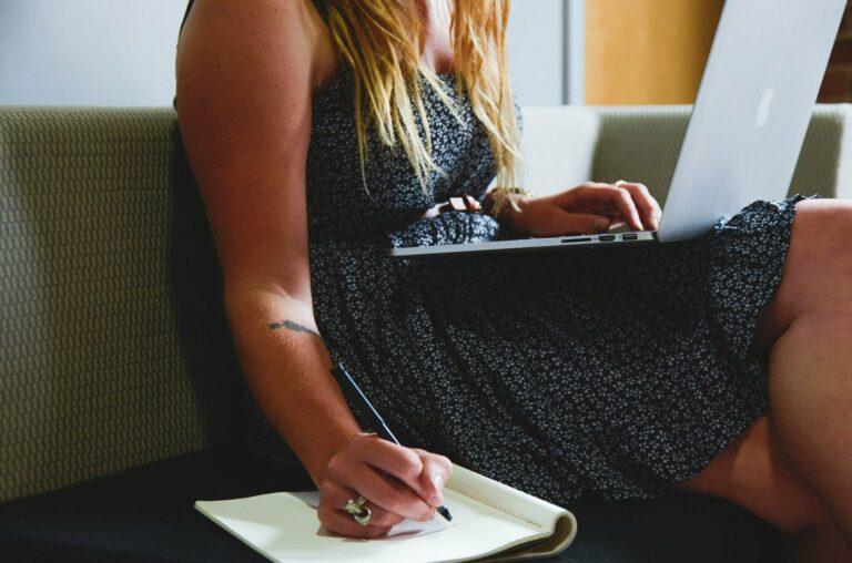 Dame alleen, op sofa met laptop op schoot terwijl aan het schrijven met pen en papier. Suggereert drang tot werken 24/7 in isolement,